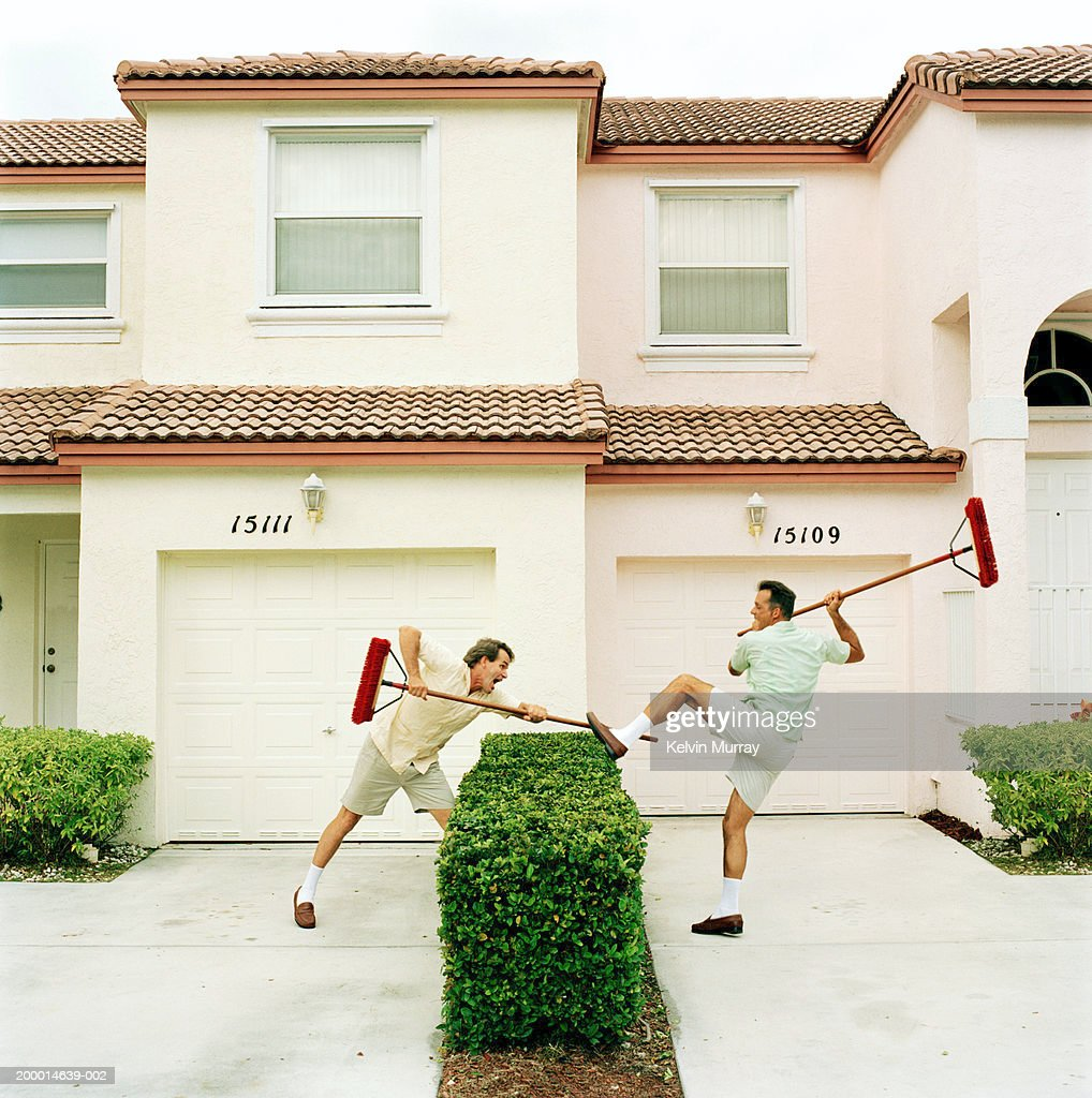 Two neighbours fighting with brooms over hedge : Bildbanksbilder