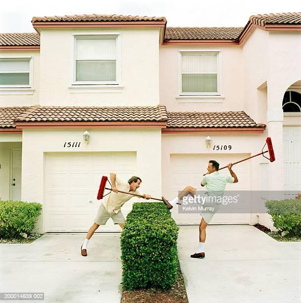 two neighbours fighting with brooms over hedge - vechten stockfoto's en -beelden