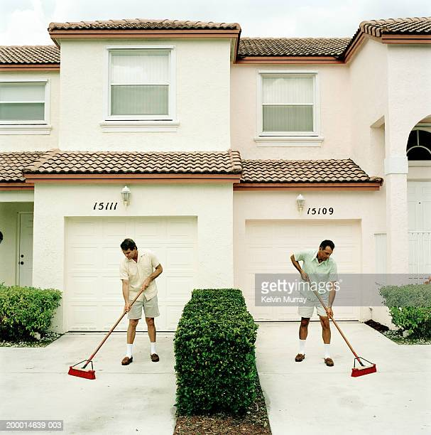 Two neighbours sweeping driveways