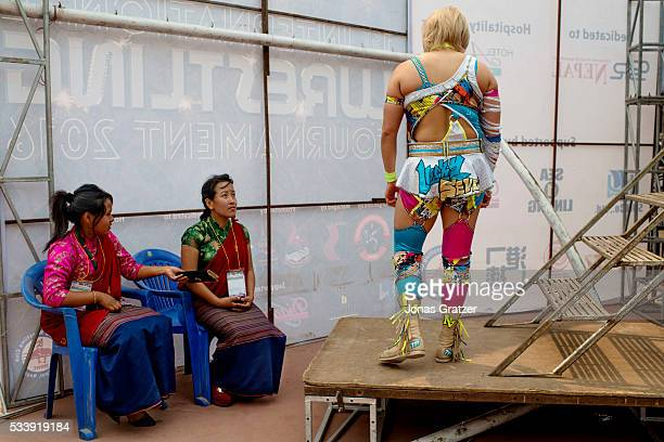 Two nepalese ladys are looking at a female wrestler from Japan The first international wrestling competition was held at Dashrath Stadium in...