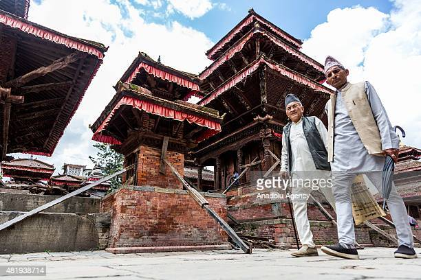 Two Nepalese men walk past a partially damaged temple in Kathmandu's Durbar square on July 25, 2015. Today marks the 3 month anniversary of the Nepal...