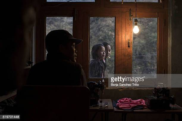 Two Nepali girls who were sleeping for several weeks in a makeshift campground after the earthquake look inside a house on their way to have dinner...