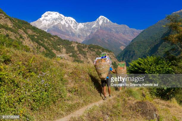 Two Nepali porters are carrying necessary stuffs to villages near the Annapurna Conservation Area, Nepal.