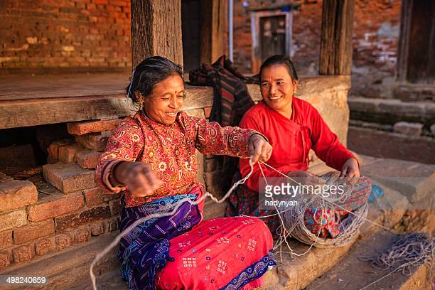 two nepali women  spinning a wool in bhaktapur, nepal - nepal stock pictures, royalty-free photos & images