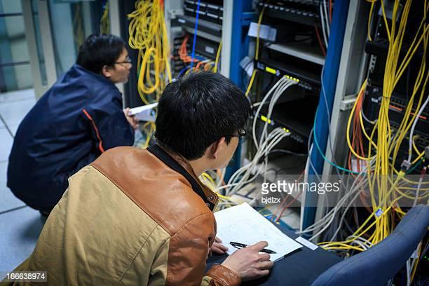 Deux réseau Les administrateurs travaillent dans la salle du serveur