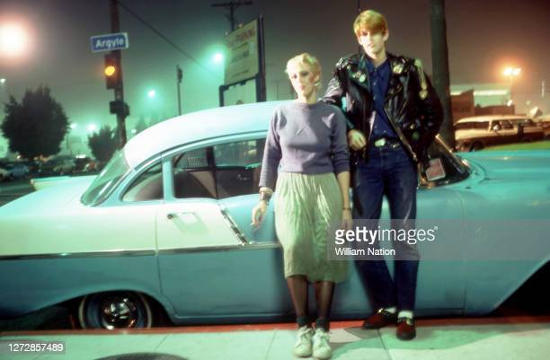 Two new wave/punk rockers stand next to a mid 1950's Chevrolet while hanging out on the corner of Argyle and Selma circa December, 1981 in Los...