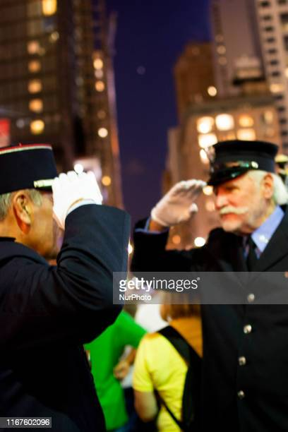 Two New York City Police Department Capitans salute each other during the Tribute in Lights at the Memorial Pool at the footprint of the World Trade...