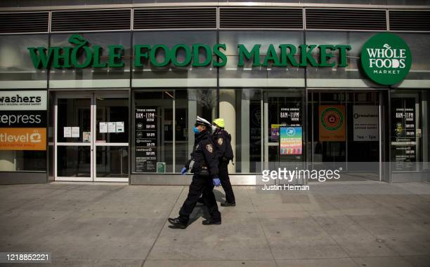 Two New York City Police Department Traffic Enforcement agents walk past the Whole Foods Market on April 14, 2020 in the Brooklyn borough of New York...