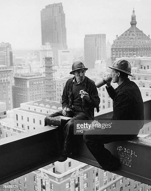 Two New York construction workers stop for lunch high above the city circa 1950