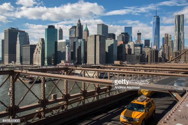 Two New York yellow taxicabs drive across the iconic Brooklyn Bridge away from Lower Manhattan, New York City, United States of America. The sky...