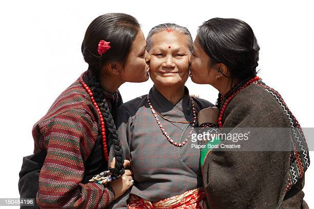 two newari sisters kissing their grand mother - nepal stock pictures, royalty-free photos & images