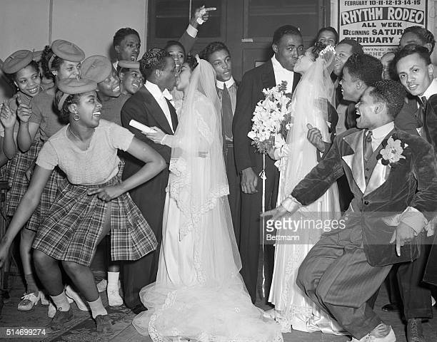 Two newlywed African American couples kiss at their double wedding to the cheers of the groomsmen and bridesmaids