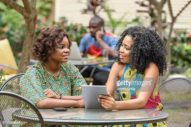 Two Nigerian women talking together with tablet