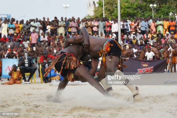 Two Nigerian wrestlers fight during a traditional wrestling festival for the nationals of the Economic Community of West African States on June 15...