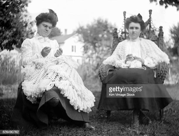 Two nimblefingered women crochet in the backyard ca 1910