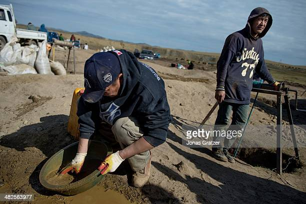 """Two """"ninja"""" men in the Sharyngol district of Mongolia soak the earth in order to find a couple grams of gold. Mongolia today is known for its large..."""