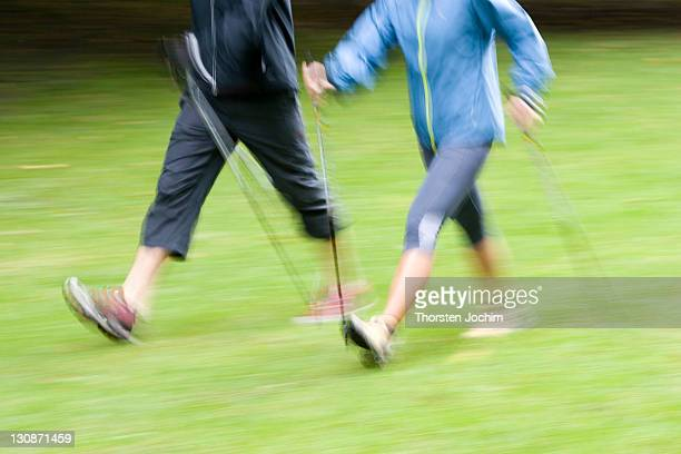 two nordic walker with stick on a green meadow in the english garden in munich as a motion study - meadow walker stock pictures, royalty-free photos & images