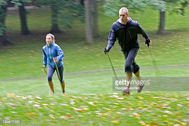 two nordic walker with sticks and sportive clothing walking uphill on a green meadow in english garden in munich - meadow walker stock pictures, royalty-free photos & images