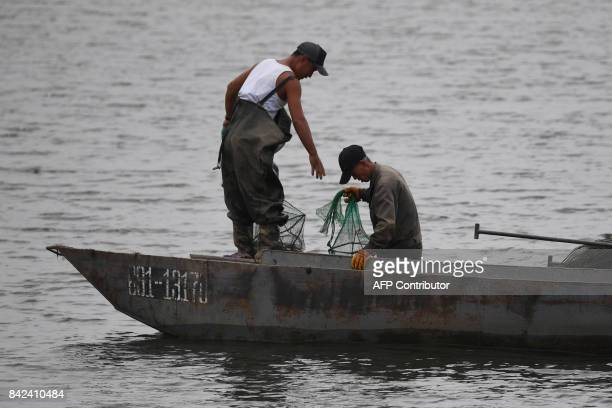 Two North Korean fishermen work on the Yalu river near the North Korean town of Sinuiju opposite the Chinese border city of Dandong in China's...
