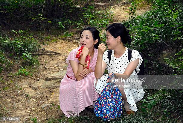 Two North Korean friends crouch down as they listen to picnickers singing songs in a park on Moranbong hill