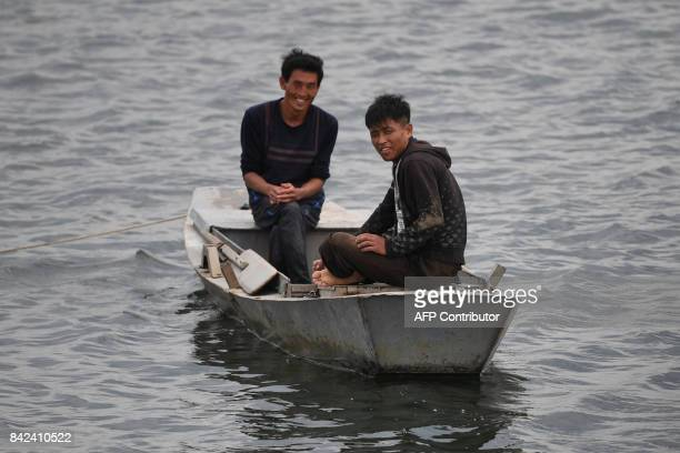 Two North Korean men smile at a boatload of Chinese tourists on the Yalu river near the North Korean town of Sinuiju opposite the Chinese border city...