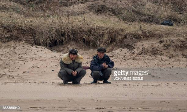 Two North Korean men with a gun sit on the bank of the Yalu river near Sinuiju opposite the Chinese border city of Dandong on April 14 2017 A...