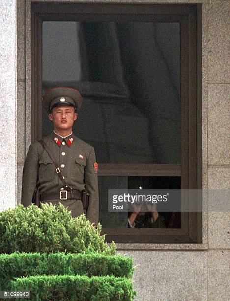 Two North Korean Soldiers Look Across The Border At Delegates Of The United Nations Command And Members Waiting On The South Side Receive Korean...