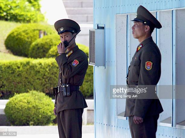 Two North Korean soldiers take up positions along the northern side of the military demarcation line at the border village of Panmunjom inside the...