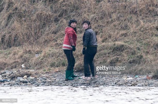 Two North Korean women stand by the riverbank of Yalu river near Sinuiju opposite the Chinese border city of Dandong on April 15 2017 China issued a...