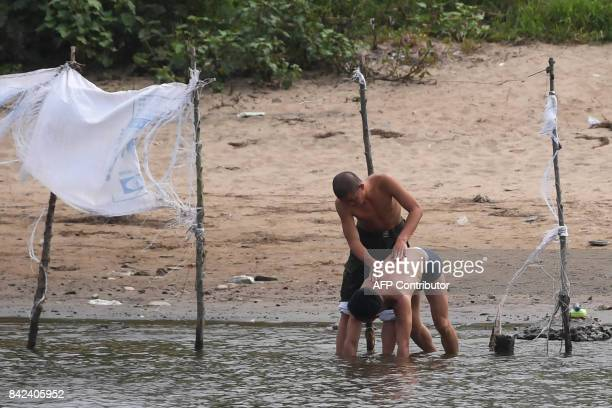 Two North Koreans help each other wash in the Yalu river near the North Korean town of Sinuiju opposite the Chinese border city of Dandong in China's...