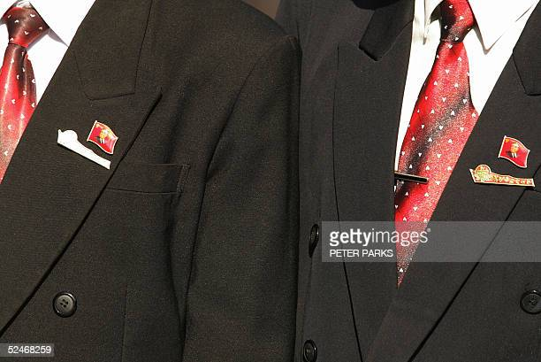 Two North Koreans wear Kim IlSung pin badges and indentical neckties in the capital Pyongyang 23 March 2005 North Korean willl play host to Bahrain...