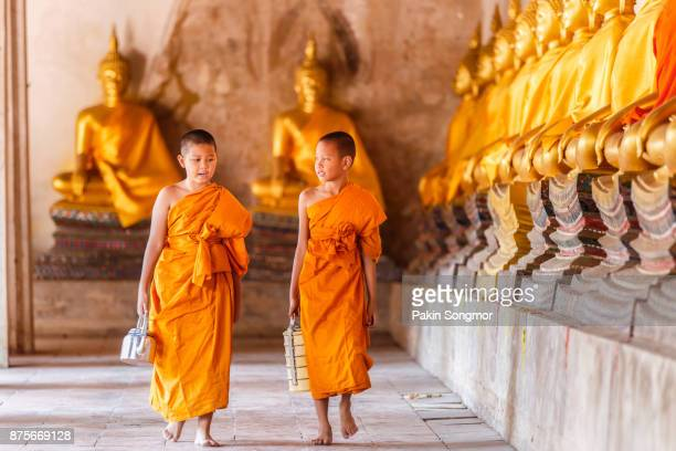 Two novices monk walking and talking in old temple at sunset time, Ayutthaya Province, Thailand