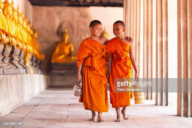two novices monk walking and talking in old temple - monk stock pictures, royalty-free photos & images