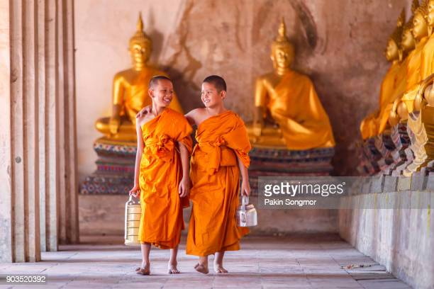 Two novices monk walking and talking in old temple