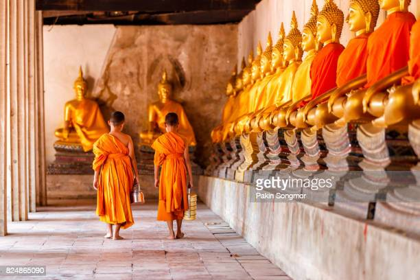 Two novices walking return and talking in old temple at Ayutthaya Province, Thailand