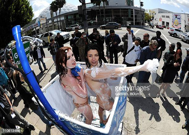 Two nude Peta girls shower on a sidewalk in Holllywood California on March 22 2011 in celebration of World Water Day to expose meat's alleged...