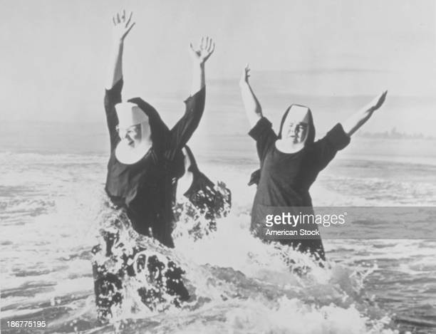 Two nuns in their habits frolicking in the ocean July 1949