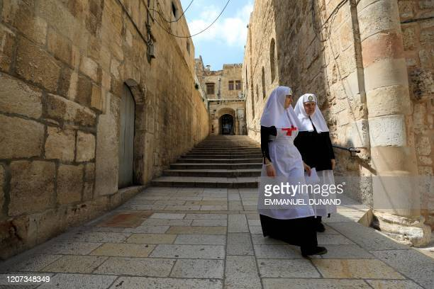 Two nuns walk in an empty street at the entrance of the Church of the Holy Sepulchre, traditionally believed to be the burial site of Jesus Christ,...