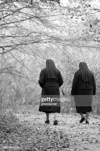 two nuns walking through park, black and white - nun stock photos and pictures