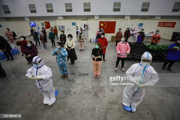Two nurses lead the line dance to encourage the patients to exercise in a temporary hospital situated in an exhibition center in Wuhan in central...