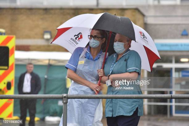Two nurses stand under an umbrella during the pouring rain outside Southend Hospital during the minute's silence for key workers who have died during...