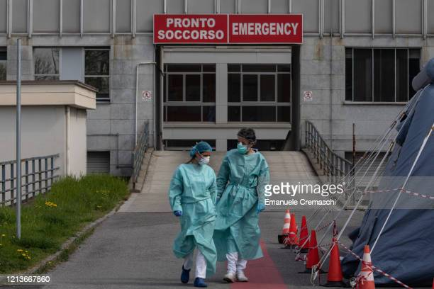 Two nurses walk in front of the Emergency Room of the local hospital on March 20, 2020 in Cremona, near Milan, Italy. The Italian government...