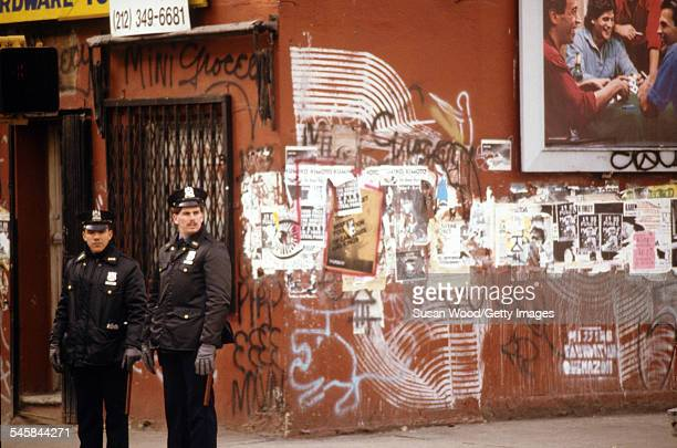 Two NYPD officers stand on a street corner on Manhattan's Lower East Side neighborhood New York New York February 1988
