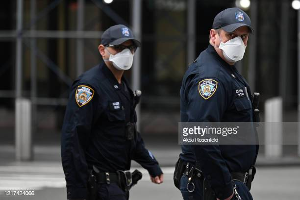 Two NYPD officers wearing 3M protective masks walk together in Times Square amid the coronavirus pandemic on April 05 2020 in New York City COVID19...