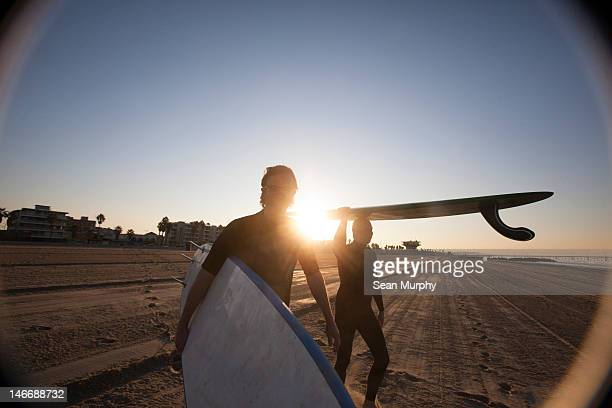 Two Ocean-Bound Surfers Head for Water at Sunrise