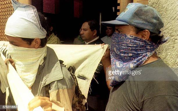Two of 15 masked gunmen talk to reporters 18 October 1993 at the gates of Managua's new cathedral as Nicaragua's Roman Catholic VicarGeneral Msgr...