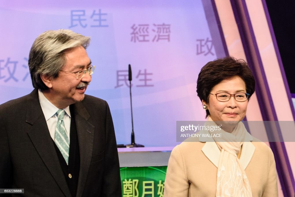 Two of Hong Kong's three leadership candidates, John Tsang (L) and Carrie Lam arrive with ex-judge Woo Kwok-hing (not pictured) at a studio before facing off in their first televised debate in Hong Kong on March 14, 2017. Hong Kong's three leadership candidates faced off in their first televised debate on March 14 as criticism mounts over a voting process which favours Beijing and bypasses the majority of the electorate. / AFP PHOTO / Anthony WALLACE