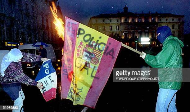 Two of some 700 Basque nationalist demonstrators burn Spanish and French flags late 25 February in Bayonne southwestern France during a demonstration...