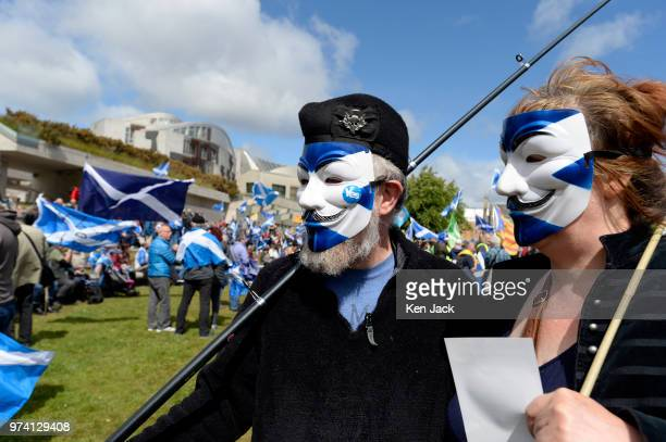 """Two of the hundreds of independence supporters demonstrating outside the Scottish Parliament, on June 14, 2018 in Edinburgh, Scotland. The """"Hands Off..."""