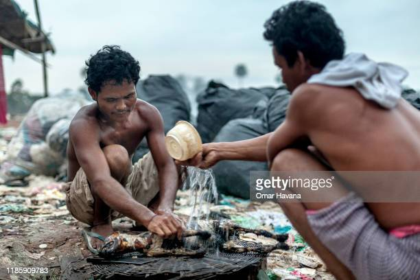 Two of the residents of the Anlong Pi rubbish dumps prepare their dinner on April 17, 2013 in Siem Reap, Cambodia. Meat is rare in their daily meals;...